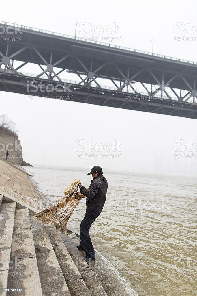 Fisherman casting net on Yangtze river with bridge behind royalty-free stock photo