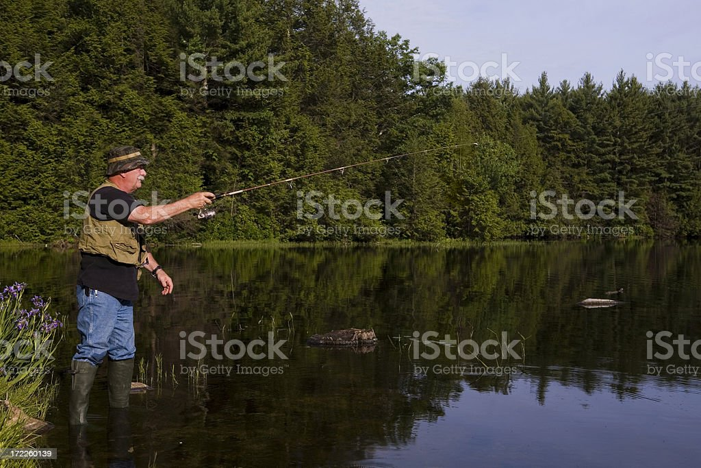 fisherman casting out royalty-free stock photo