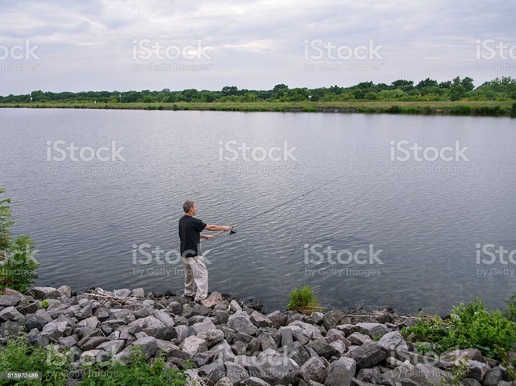 Fisherman catches fish. Concept of rural getaway stock photo