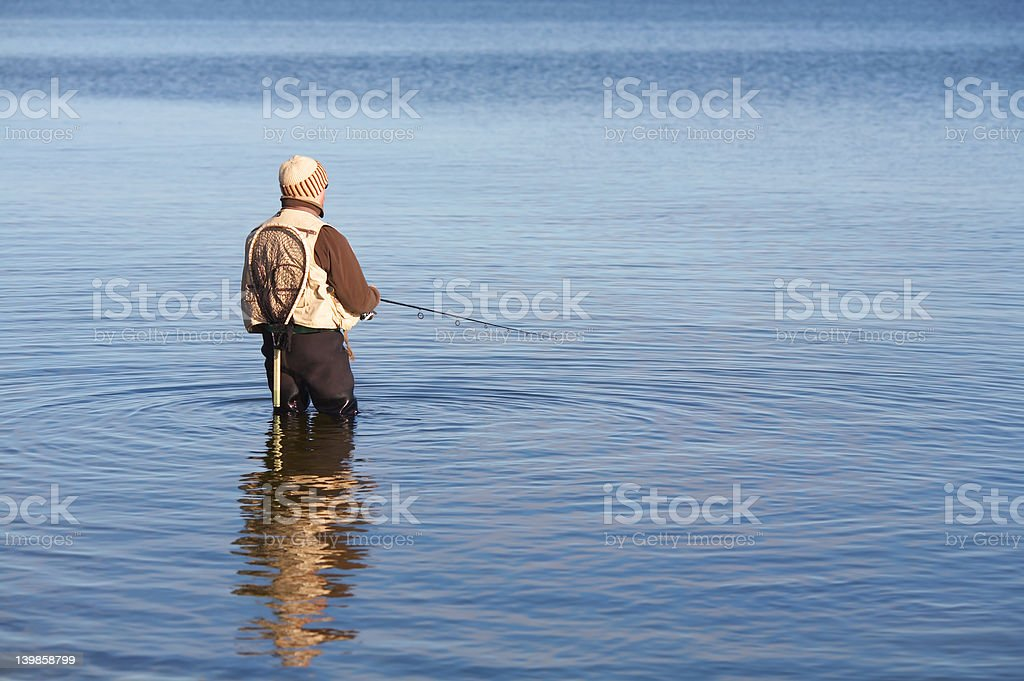 Fisherman catching fish in a lake royalty-free stock photo