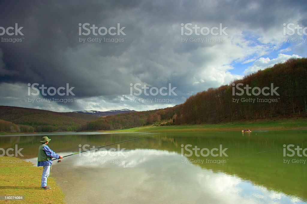 Fisherman catching fish on a lake royalty-free stock photo