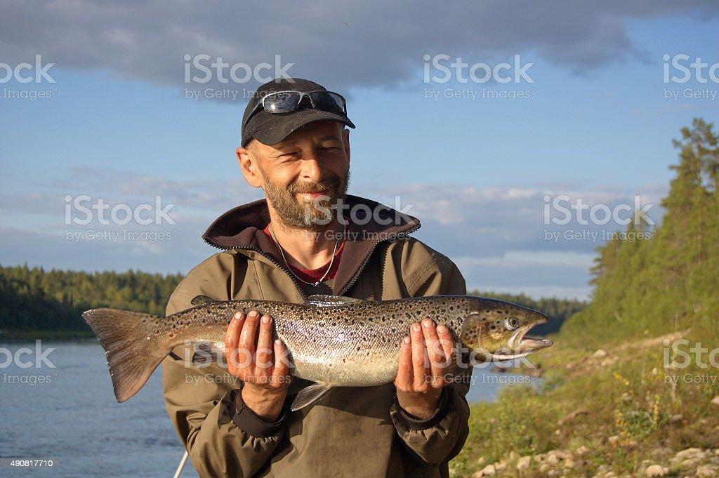 Fisherman caught a big salmon. stock photo