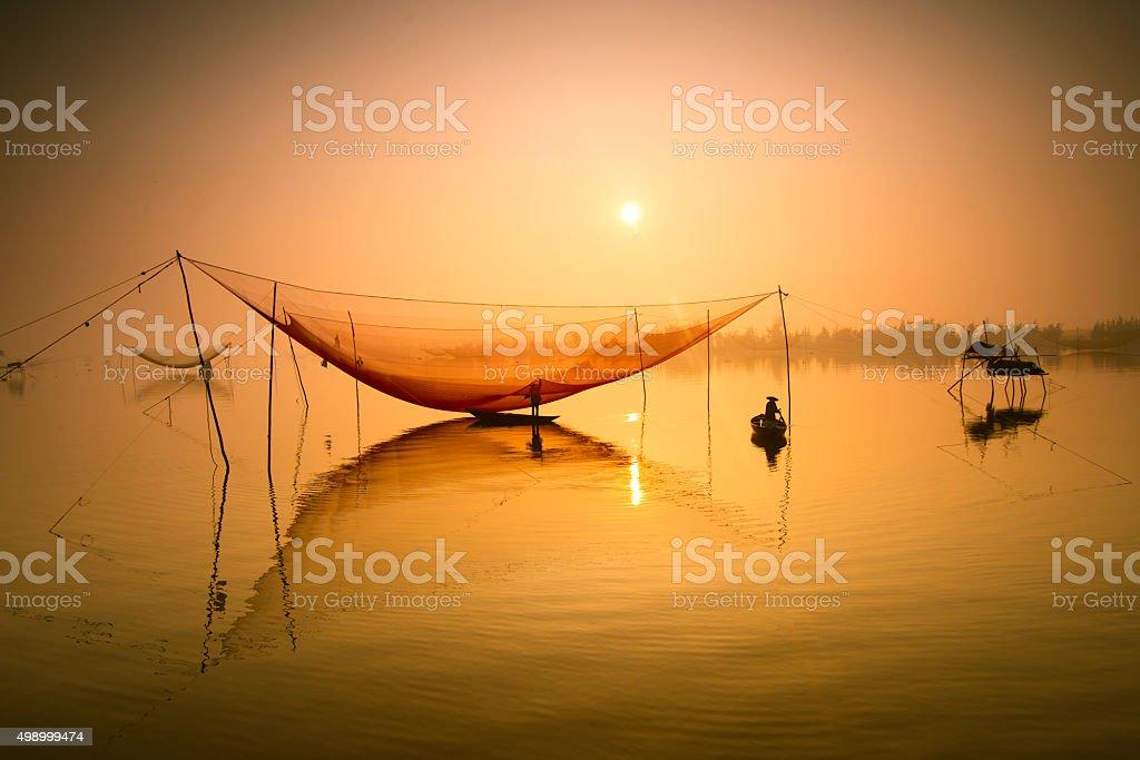 Fisherman checks his nets on river in Hoian, Vietnam stock photo