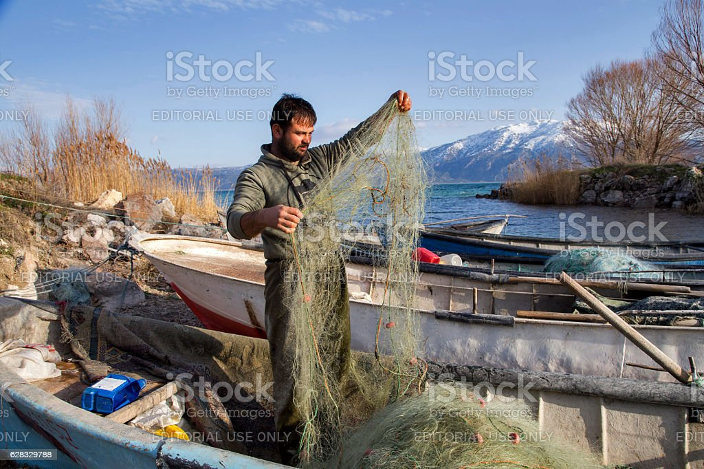 Fisherman collects crayfishes from his net in Egirdir Lake. stock photo