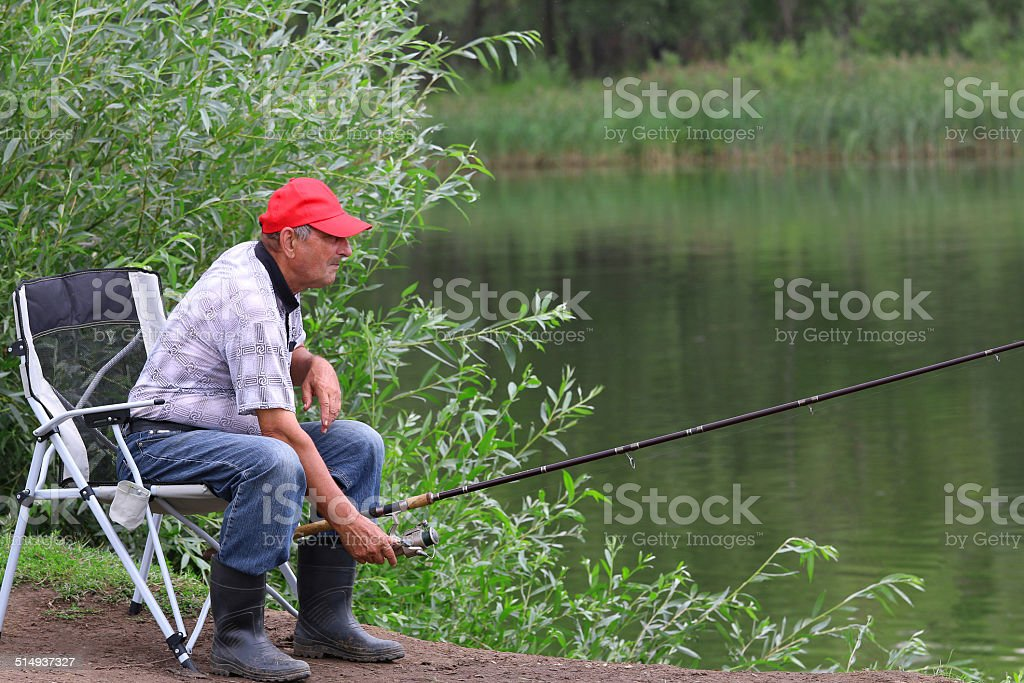 Fisherman fishes in the river. Middle aged man. stock photo