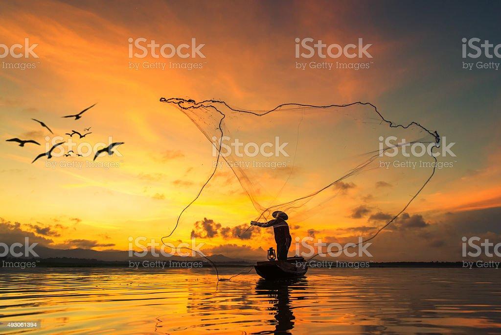 Fisherman fishing at lake in Morning, Thailand. stock photo
