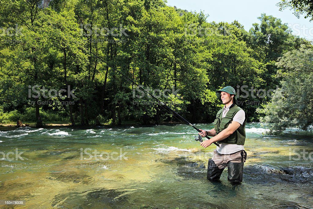 Fisherman fishing on a river with forest in the background stock photo