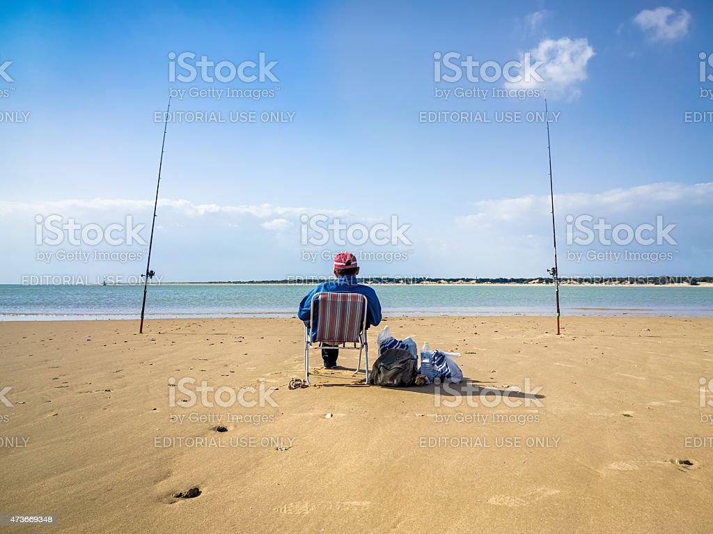 Fisherman pesca em uma praia vazia foto royalty-free