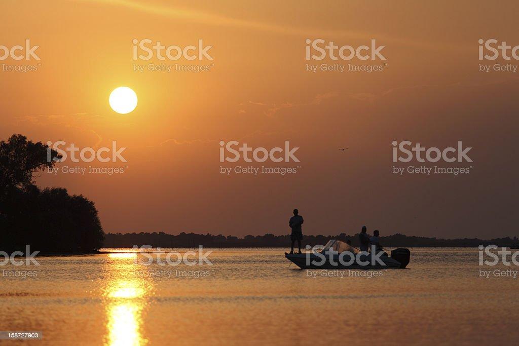 Fisherman fishing on the lake in sunset stock photo