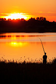 Fisherman fishing with a rod at sunset