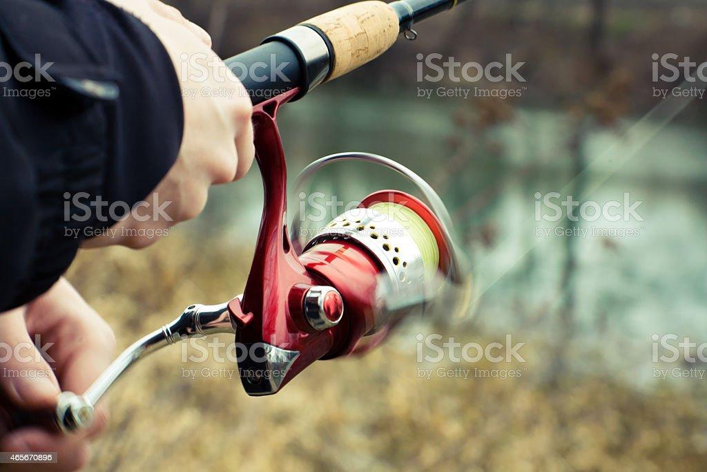 Fisherman hang to turn reel. stock photo