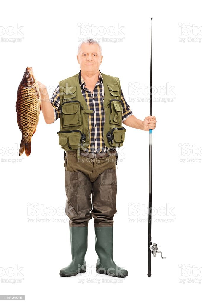 Fisherman holding a fish and fishing rod stock photo
