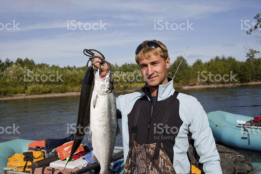 fisherman holding a fresh caught fish royalty-free stock photo