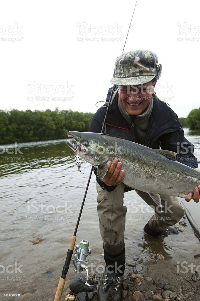 fisherman holding a fresh caught fish stock photo