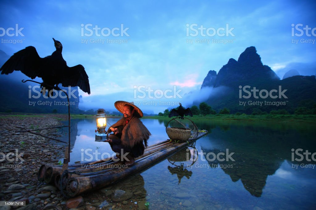 Fisherman holding flashlight and two crows stock photo