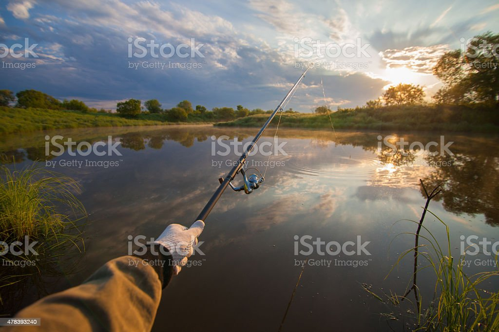 Fisherman holding his fish-rod stock photo