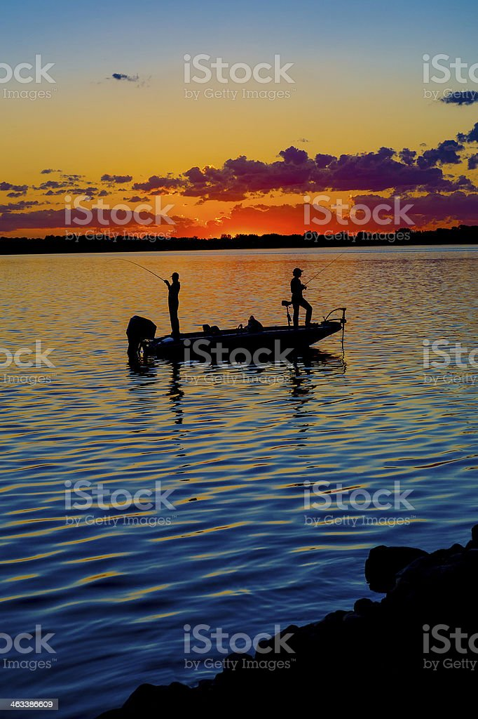 Fisherman In A Boat At Sunset stock photo