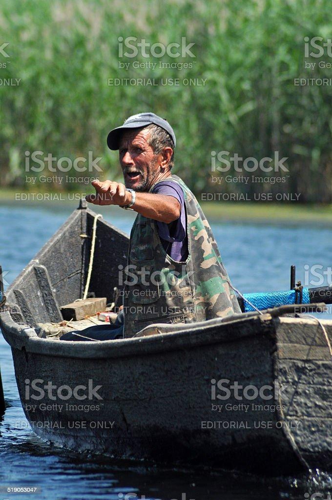 Fisherman in a boat in the Danube delta, Romania stock photo