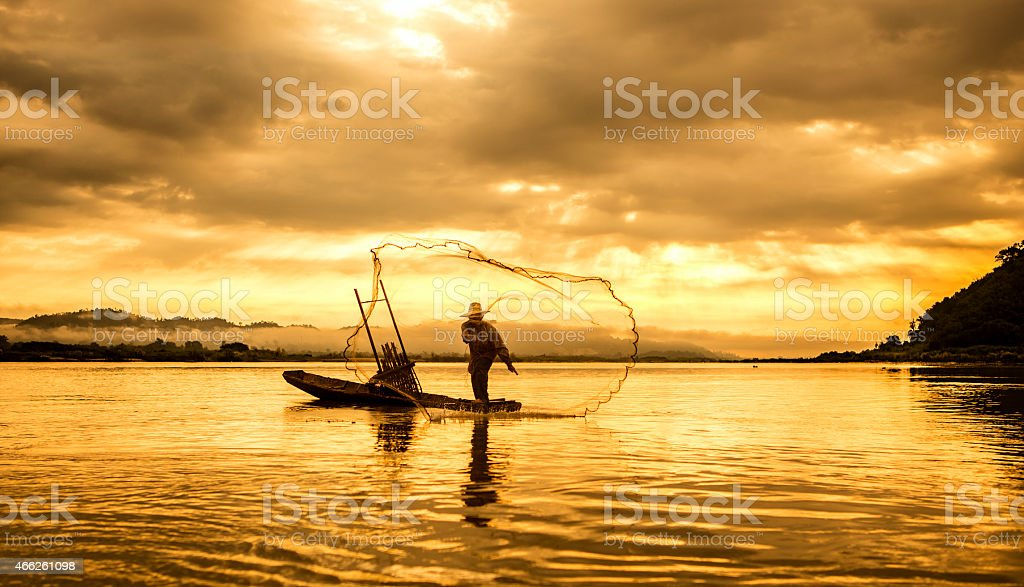 A fisherman in a boat on the lake at sunset stock photo