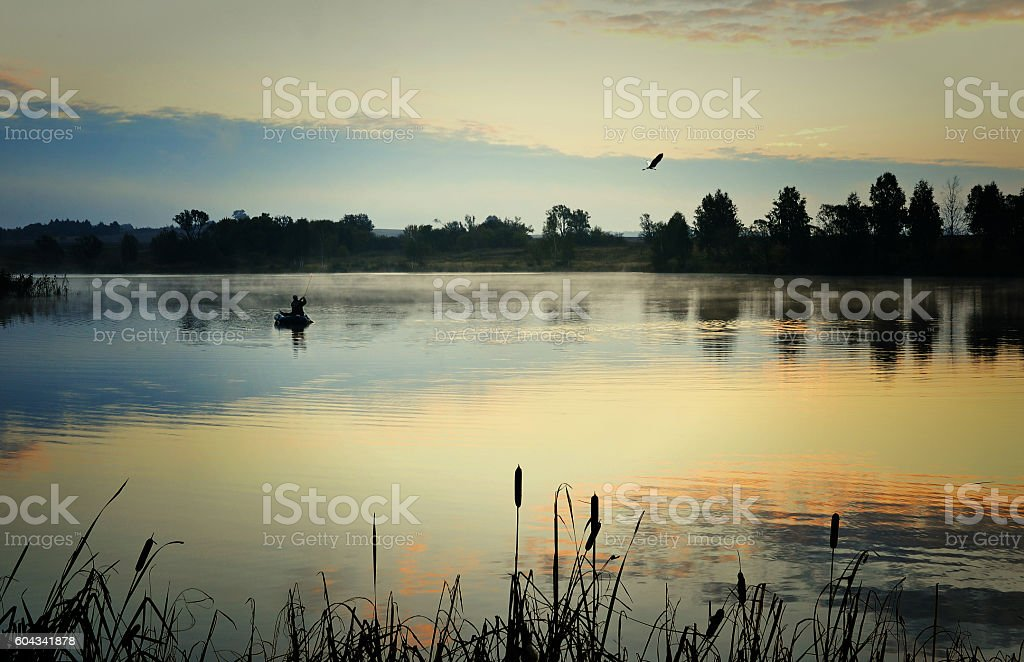 Fisherman in a boat sailing in the morning mist stock photo