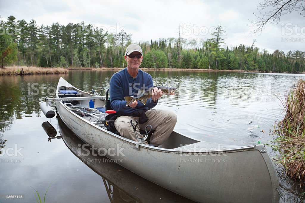 Fisherman in a canoe on a lake shows a walleye stock photo