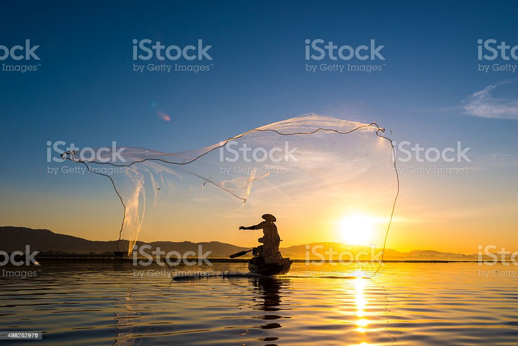 Fisherman in action during fishing in morning stock photo
