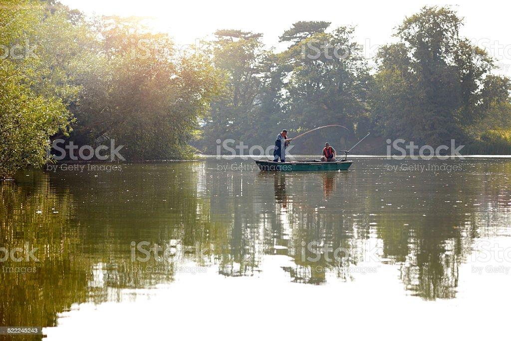 Fisherman in bass boat enjoying fly fishing stock photo