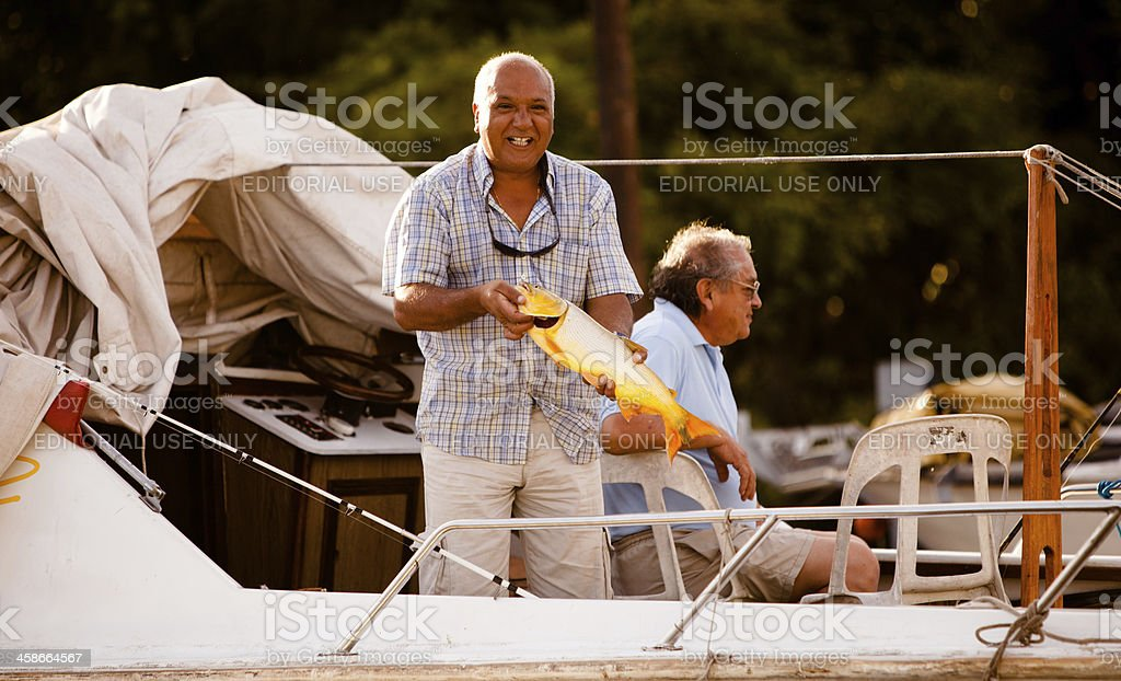 Fisherman in Buenos Aires showing off his fish royalty-free stock photo