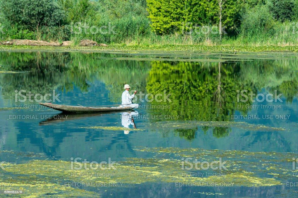 Fisherman in his shikara canoe on Lake Dal, India stock photo