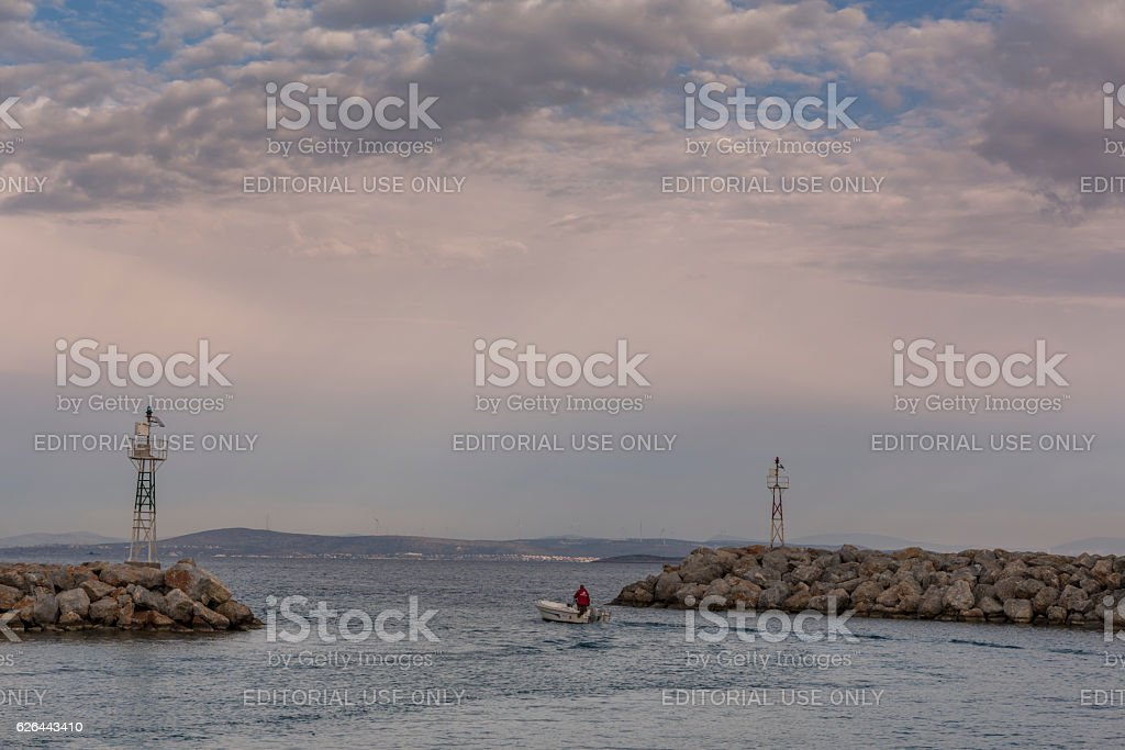 Fisherman in small boat leaving Chios harbor stock photo