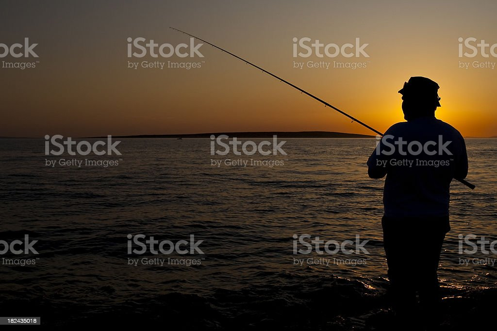 Fisherman in sunset royalty-free stock photo