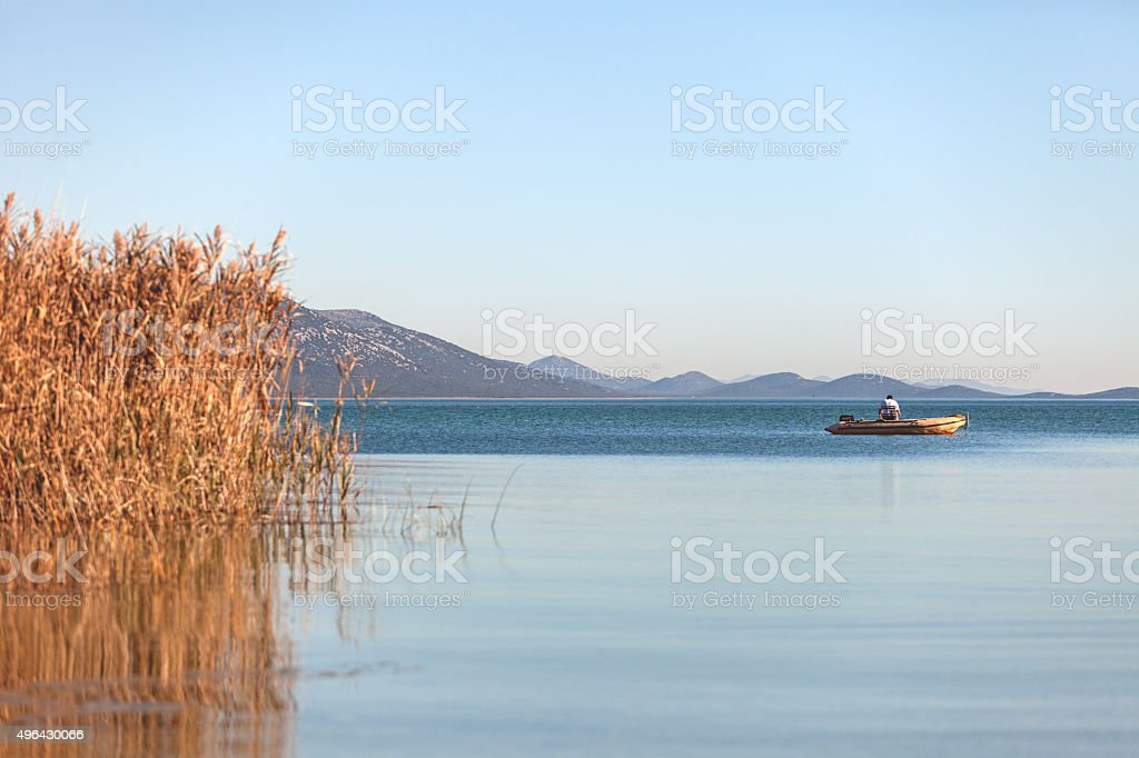 Fisherman in the boat on the lake stock photo