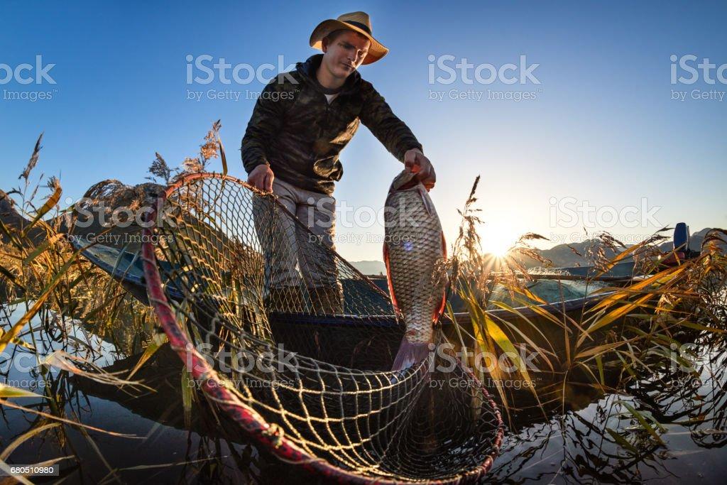 Fisherman in the boat stock photo