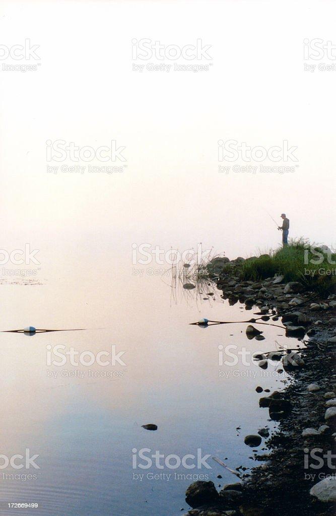 Fisherman in the fog stock photo