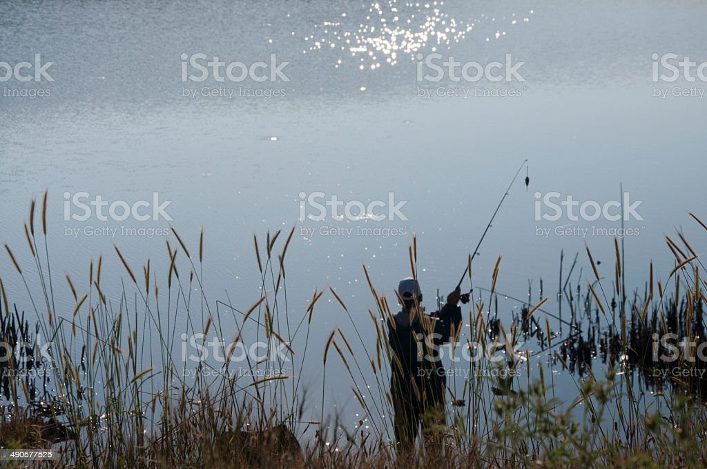Fisherman in the lake stock photo