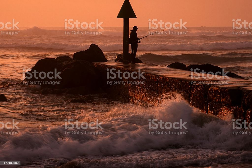 Fisherman in the sunset stock photo