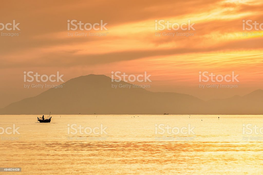 Fisherman in Traditional Boat at Sunset, Vietnam stock photo