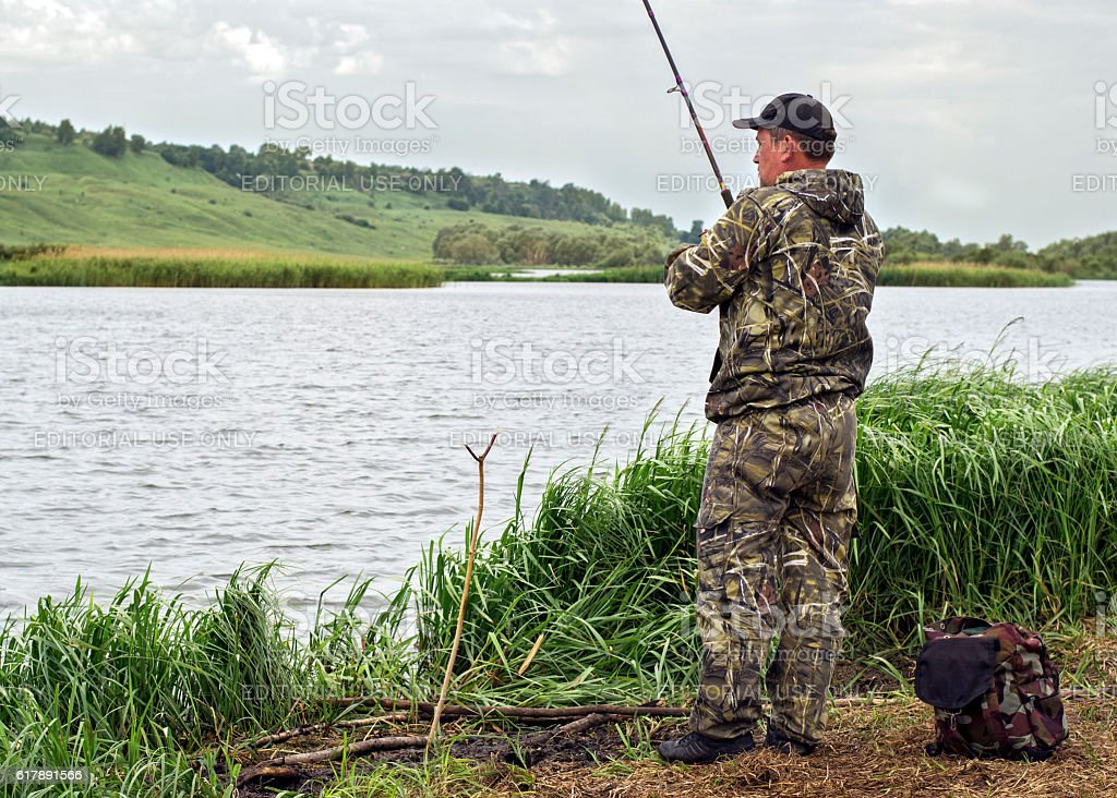 Fisherman is fishing from the shore stock photo