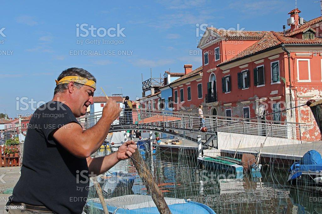 Fisherman is repairing fishing net near Venice sea canal stock photo