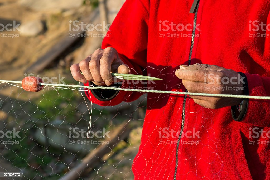 fisherman knits fishing nets - selective focus, copy space stock photo