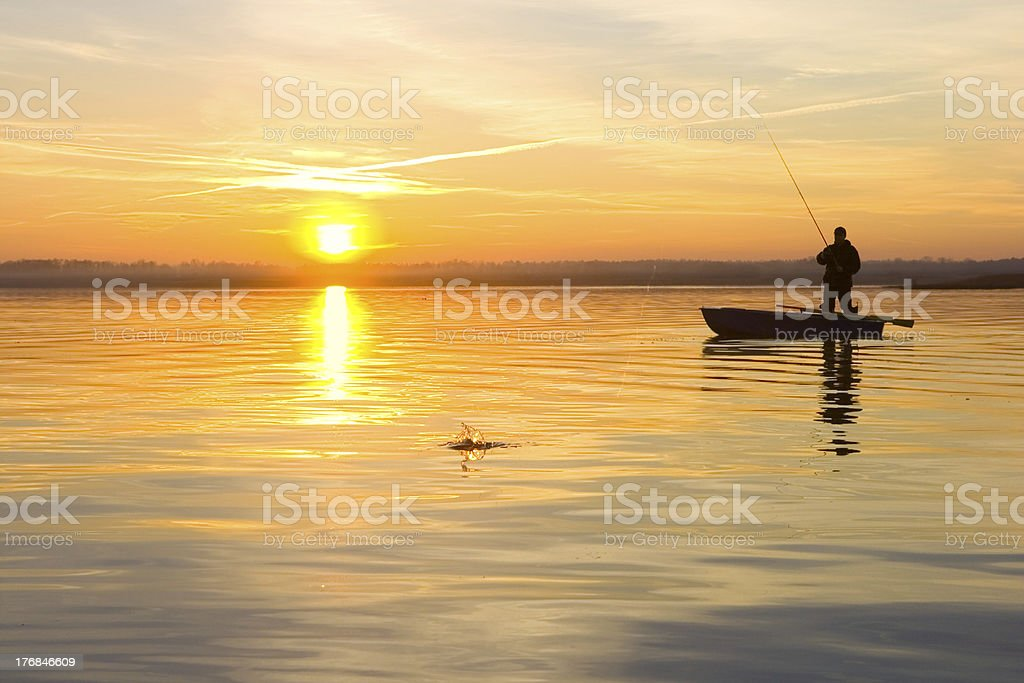Fisherman on a boat at sunset stock photo