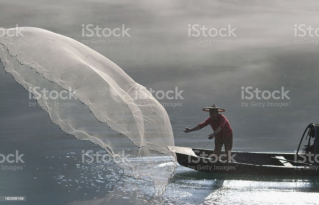 Fisherman on a boat casting out a net stock photo