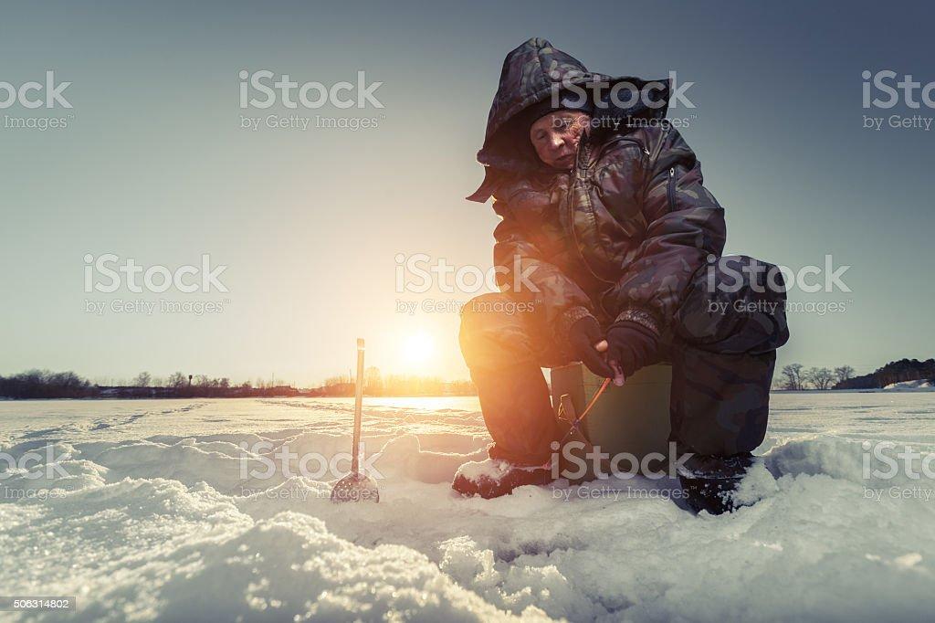 Fisherman on a winter lake stock photo