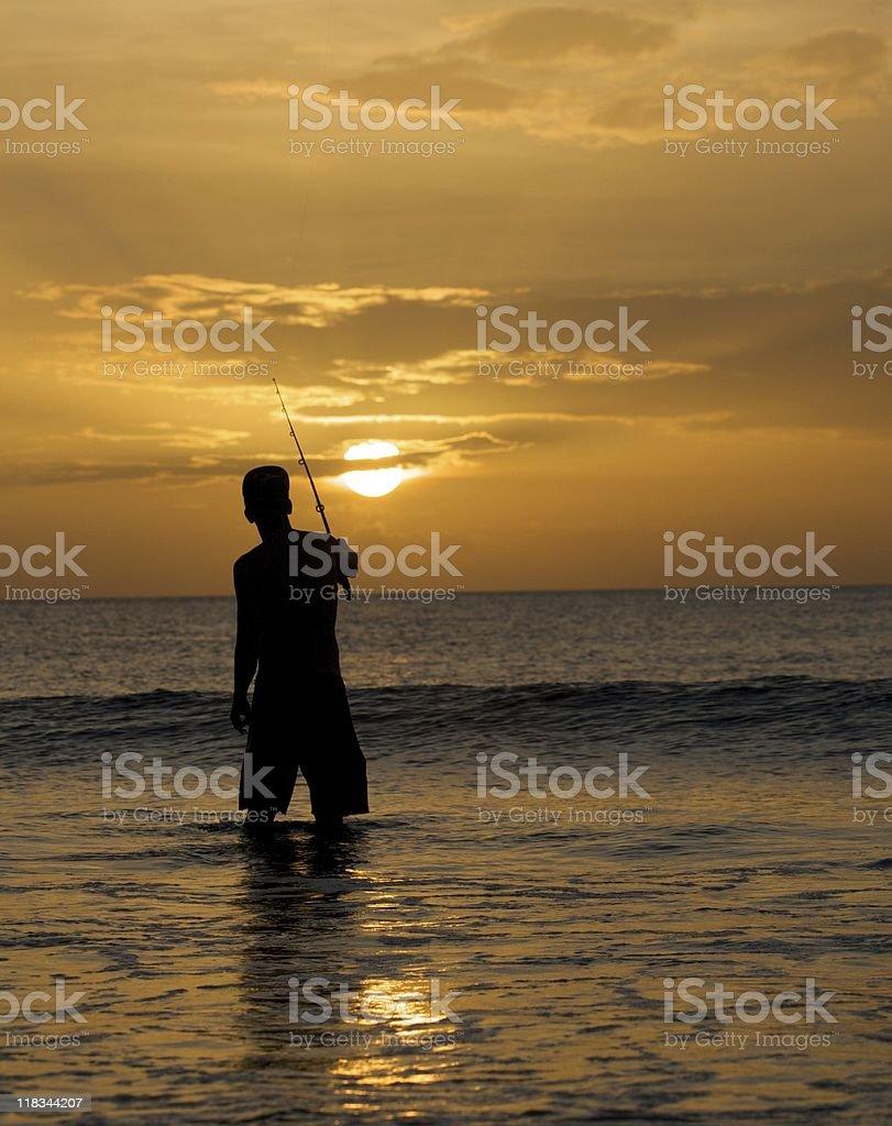 fisherman on beach during sunset royalty-free stock photo