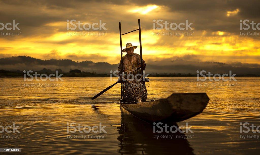 Fisherman on boat catching fish stock photo