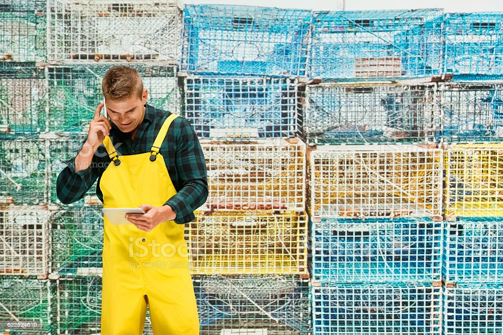 Fisherman on phone in front of fishing industry stock photo