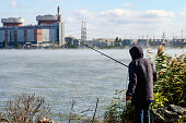 fisherman on the background of the nuclear power plant