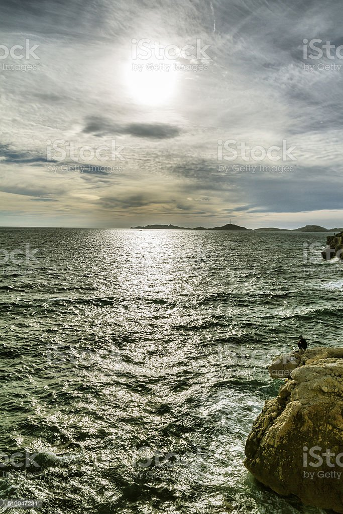 Fisherman on the cliff at sunset stock photo