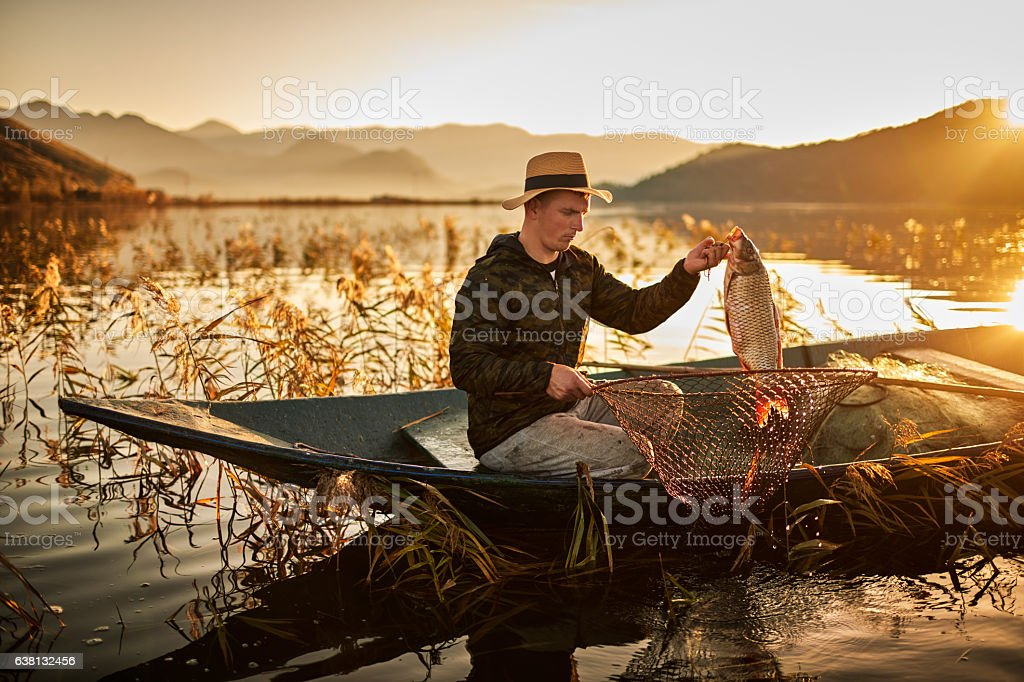 Fisherman on the lake at sunset stock photo