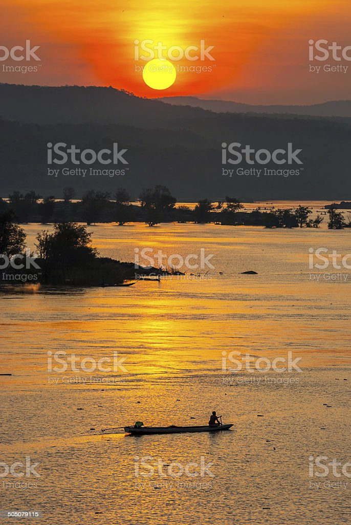 Fisherman paddling rowboat to fishing with sunset, Silhouette stock photo